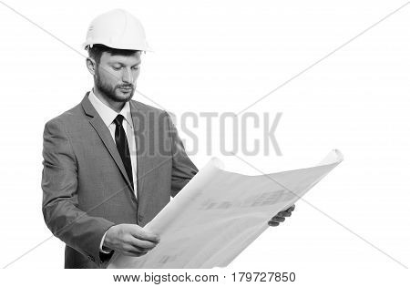 Paperwork. Successful male architect wearing hardhat holding a blueprint studying it checking examine urbanization future building project plan planning professionalism trustworthy concept monochrome