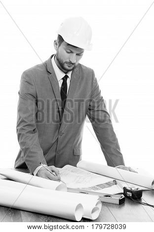 Perfecting the project. Black and white studio shot of a professional mature male real estate manager in a hardhat working on building plans businesspeople businessman profession development concept