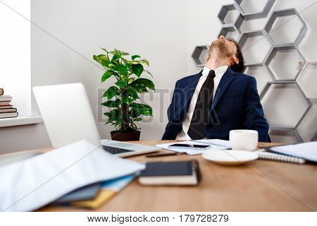Young tired businessman in suit sitting at workplace, rolling head, office background.