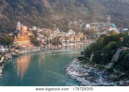 View of River Ganga and Lakshman Jhula bridge at sunset with a colorful jungles on a background and colorful houses. Rishikesh. India.