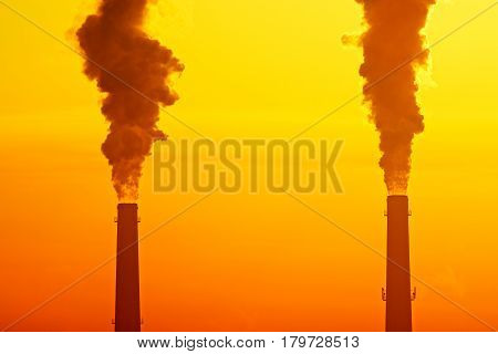 Two industrial pipes with smoke against sunrise or sunset sky. Smog pollution concept and global warming concept