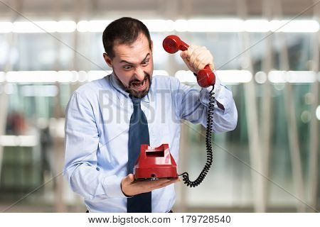 Angry man hanging the telephone down