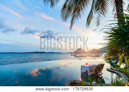 Romantic luxury dinner setting at tropical resort on sunset