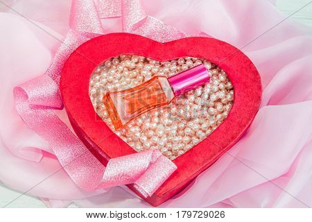 Red glass perfume bottle in a heart shaped box with pink pearl beads. Romantic present.