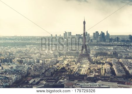 Paris skyline with Eiffel Tower at sunset on a cloudy day. La Defense business district can be seen in the distance behind the tower.