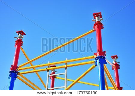 Colorful new scaffolding against bright blue sky