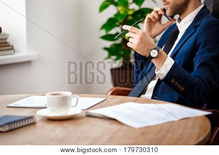 Close up of young successful businessman speaking on phone at workplace, office background.