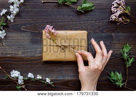 Female Hand Unpacking Gift Box Wrapped With Craft Paper And Flowers On The Wooden Table Top View. Gi