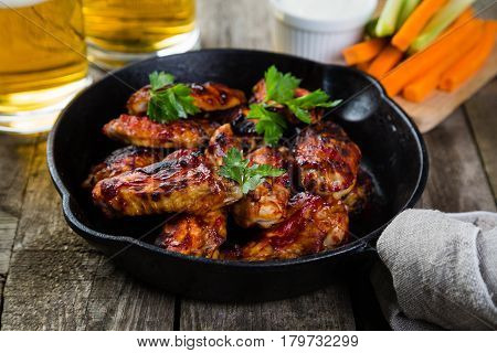 Chicken wings in cast iron skillet, rustic wood background