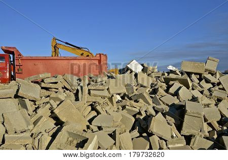 A pile of broken concrete building blocks are waiting to be loaded into a truck box by a excavating bucket