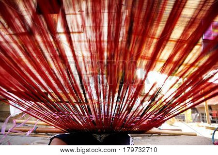 Woman weaving red threads with hands on weaving device seen from a low angle view in Flores Samosir.