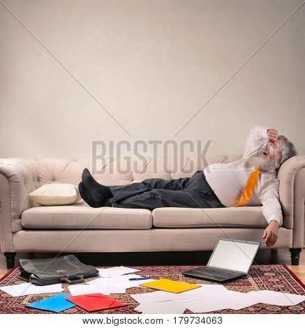 Stressed out elderly employee lying on the sofa after a long day of work