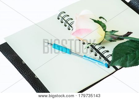 Notebook , pen and artificial rose isolated on white background