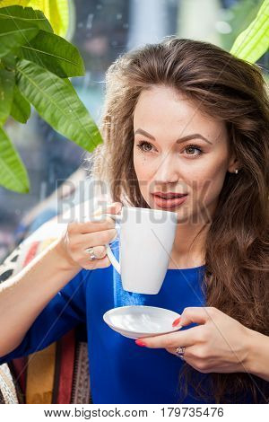 Woman holding a cup of coffee. Coffee drinker.