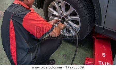 A car mechanic unscrewing a wheel  in the garage