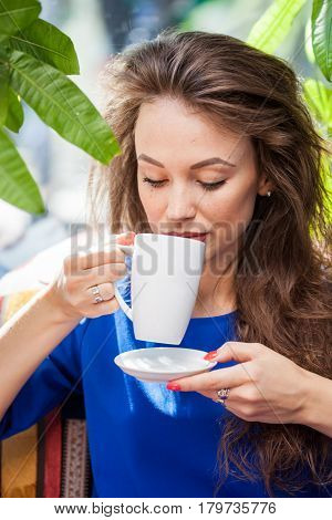 Beautiful woman holding a cup of coffee. Coffee drinker.