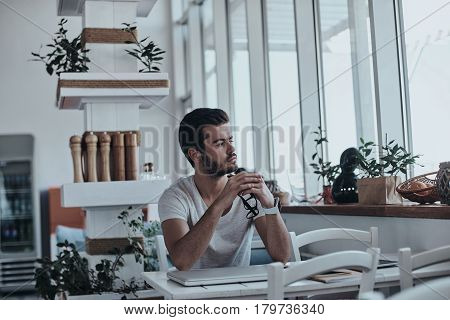 Daydreamer. Thoughtful young modern man keeping hands clasped and looking away while sitting at the table in cafe