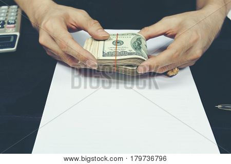 Male 's hands holding folded U.S dollar bills