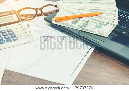 Finance concept : The United States hundred-dollar bills calculator bills eyeglasses pen and laptop on the table