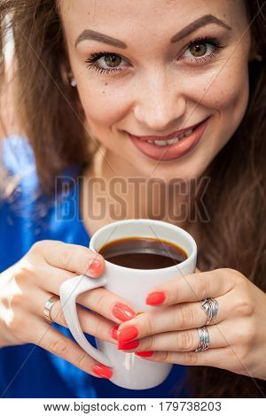 Beautiful smiling woman drinking a cup of coffee. Coffee drinker.