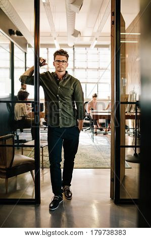 Full length portrait of young man standing in doorway of startup office with people working in background.