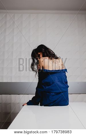 Slender brunette with henna ornaments drawn on her back sitting on a white table
