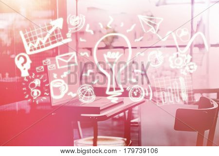 Laptop on a table against digital generated image of light bulb amidst business icons 3d
