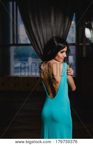 Slender brunette in a turquoise dress with henna ornaments drawn on her back