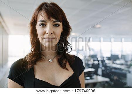 Portrait of confident mature businesswoman standing in office. Caucasian female entrepreneur looking at camera.