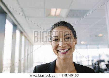 Portrait of beautiful mature businesswoman standing in office and smiling. Asian female entrepreneur looking at camera with big smile on her face.