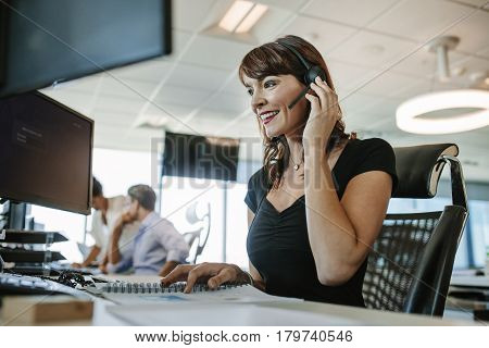 Beautiful mature business woman talking on headset while working at her desk. Caucasian female executive with people working in background.