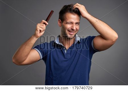A handsome young man feeling happy and winking while combing his hair