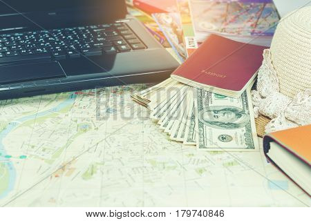 Traveling concept : Passport , books , map , U.S. dollar bills laptop , notebook and woven hat