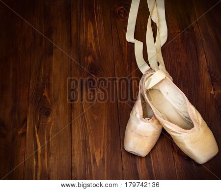 Pink old used pointe shoes on wood background
