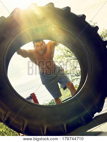 Man doing fitness training with huge tyre outdoors, looking through the tyre, backlit lensflare.