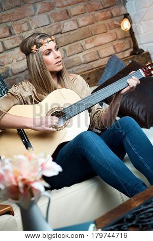 Young hippie girl playing the guitar at home.