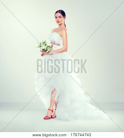 Beauty fashion Young model Bride in white wedding dress with long train and bouquet of flowers posing in studio. Salon. Beautiful fiancee in elegant dress, perfect makeup and hairstyle. Full length
