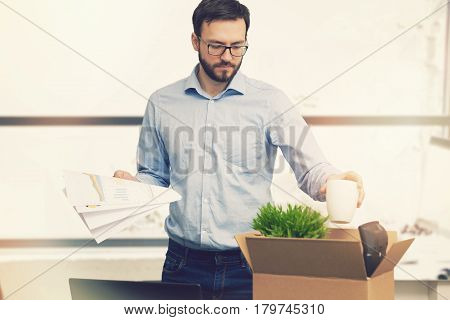job loss - fired man putting his belongings in cardboard box