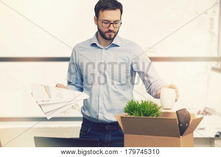 job loss - fired man putting his belongings in cardboard box