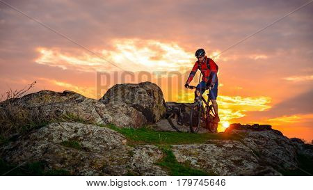 Cyclist Riding the Mountain Bike on the Spring Rocky Trail at Beautiful Sunset. Extreme Sports and Adventure Concept.
