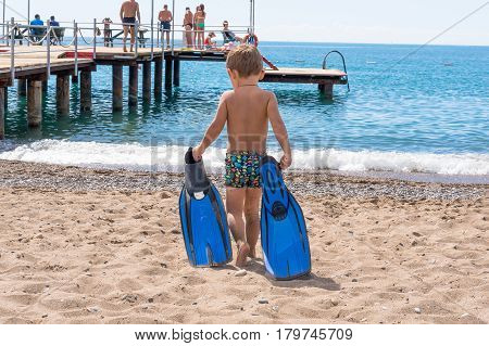 Adorable little blond kid boy having fun on tropical beach. Excited child playing and surfing in sun protected swimsuit in ocean on vacations. White sand Kid holding flippers for swimming