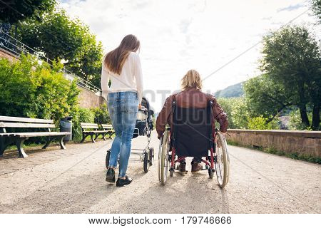 Young parents with father sitting in wheelchair enjoying time outdoors, taking their baby to a park along the banks of the river Neckar in Heidelberg, Germany.