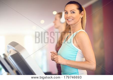 Attractive middle-aged woman in a mint top standing on treadmill in the gym looking at camera and smiling with copy space