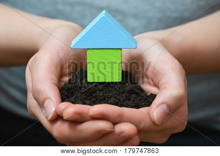 Female hands holding a piece of land with wooden house. Ecological home, construction and real estate concept
