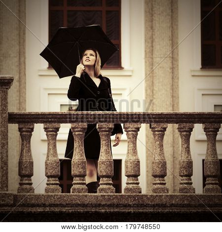 Happy young woman with umbrella walking on city street. Stylish fashion model in black coat outdoor