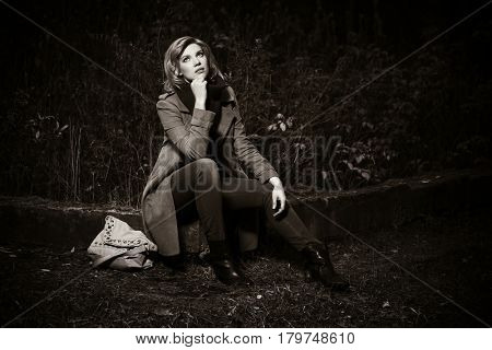 Young blond woman in classic coat in autumn forest. Stylish fashion model outdoor