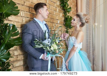 Newly married couple loving couple before the wedding. Man and woman loving each other. The bride in the turquoise dress and groom in a blue suit. Wedding decor wedding photo zone