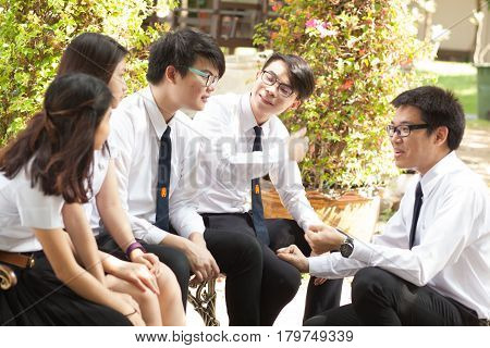 Bangkok, Thailand - November 17, 2015 :  King Mongkut's Institute of Technology Ladkrabang is a research and educational institution in Thailand. A group of student have fun talking and playing in the garden.