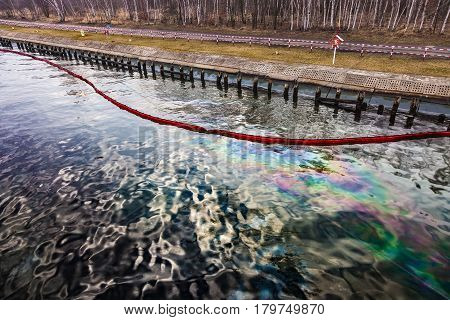 Floating oil boom with oil spill on the water - environment pollution.