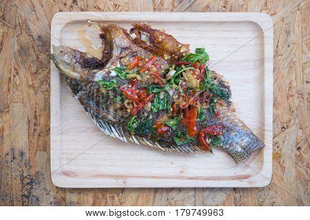 Deep fried fish dressing sweet chili sauce on wood tray